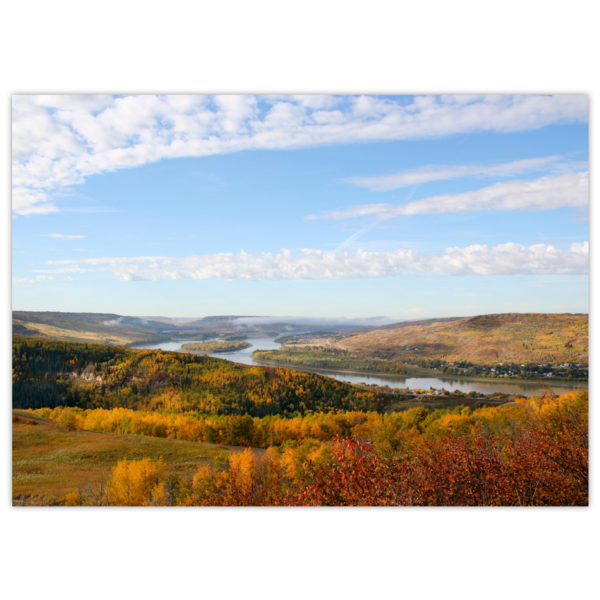 blue sky framed with white clouds on a sunny day over the Peace River valley in the glory of autumn