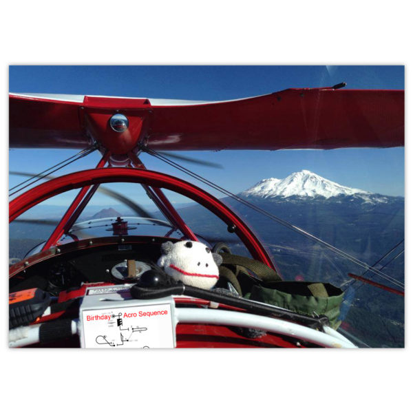 a sock monkey rides in the front seat of a red Pitts bi-plane with snow-capped mountains in the background