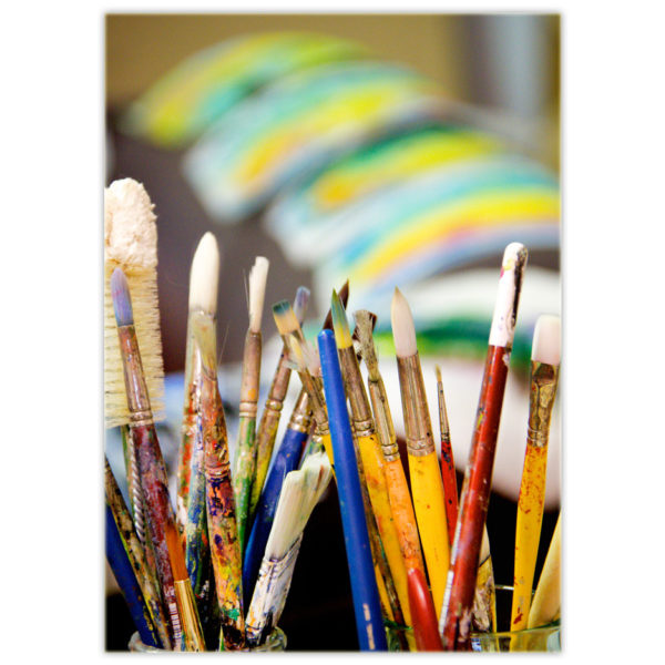 an artist's paintbrushes are displayed like two beautiful bouquets of flowers with art drying in the background