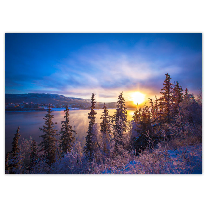 brilliant blue, pink and yellow sunrise over the Peace River on a very cold winter day with frosty evergreen trees in the foreground and steam rising off the river
