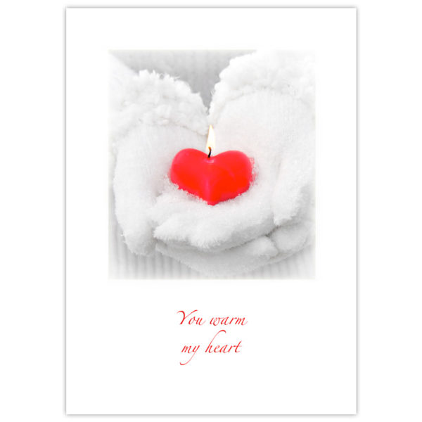 white fluffy snow-covered winter gloves worn by a woman holding a red heart-shaped candle with a flame