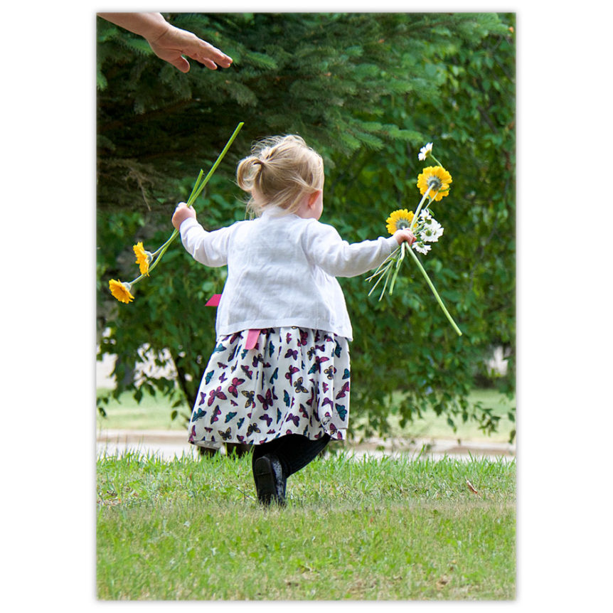 little girl running with daisies in her hands