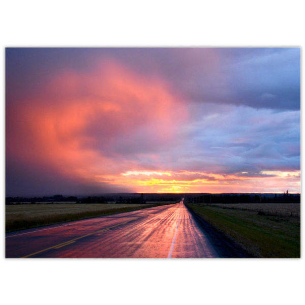 sunset reflecting off a swirl of cloud rising up over a wet shiny highway