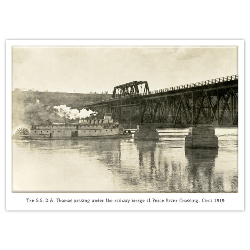 S.S. D.A. Thomas stern-wheel paddleboat passes under the railway bridge at Peace River Crossing, 1919.