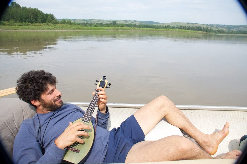 Tree planter playing a ukulele while floating down the river