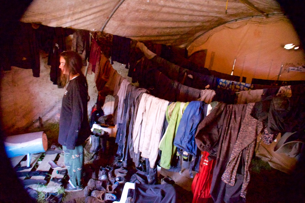 "muddy wet clothes drying on multiple clothes lines in the ""dry"" tent at a tree planters campe"
